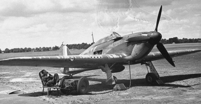 Авиатехник отдыхает в тени крыла истребителя «Харрикейн». 1940 г.