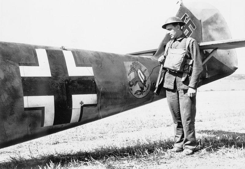Ополченец у Messerschmitt Bf 109E-4, который совершил аварийную посадку в Ист-Лэнгдоне в Кент. 24 августа 1940 г.