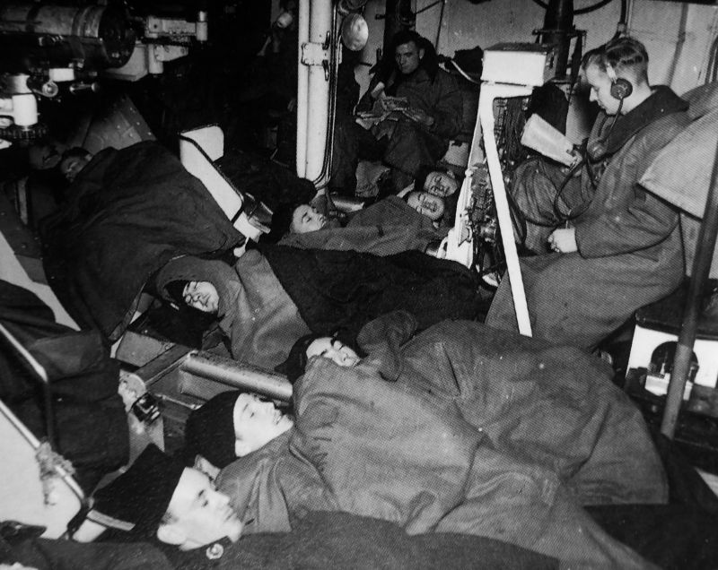 Матросы легкого крейсера «Шеффилд», спящие в орудийной башне с 152-мм орудиями. 1941 г.