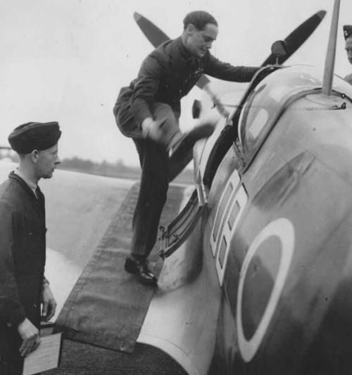 Английский ас Дуглас Бэйдер на протезах забирается в кабину истребителя «Спитфайр» Mk.IX. 1941 г.