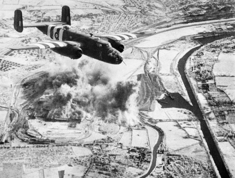 Бомбардировщик Норт-Американ «Митчелл» Mk II над окутанным дымом сталелитейным заводом «Металлургической компании Нормандии» в пригороде Кана. 22 июня 1944 г.