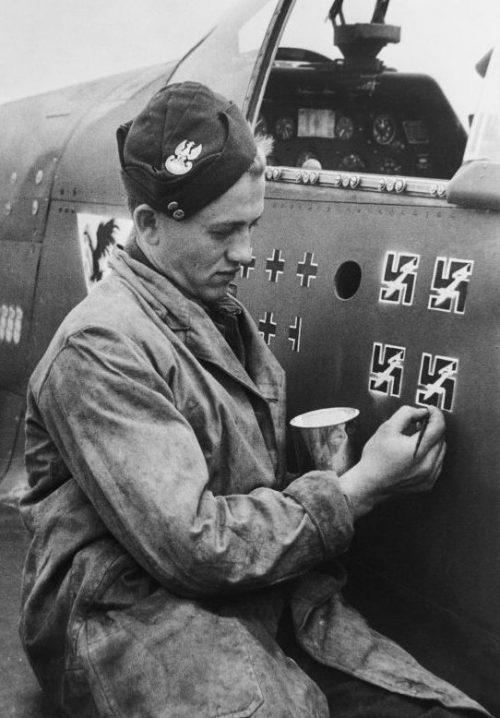 Механик наносит отметки о победах на борт самолета польского аса Евгениуша Хорбачевского. 3 августа 1944 г.
