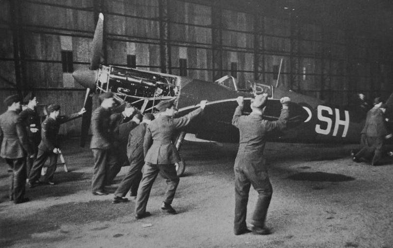 Персонал аэродрома закатывает истребитель «Спитфайр» в ангар.1944 г.